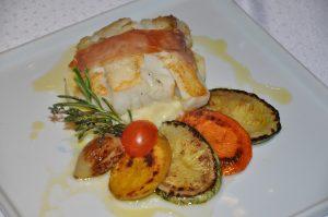 Posta de bacalhau envolto de Parma, purê de echalote e legumes grelhados no azeite aromatizado, prato do L'Ô Restaurante (Irauã Freitas)