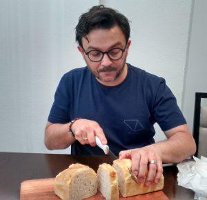 Karliano partindo seu delicioso coupiac, pão tradicional europeu com toques de queijo